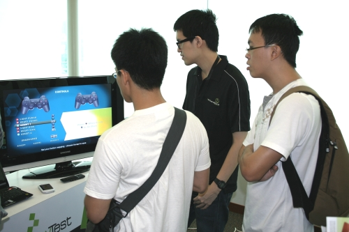 James Lu, GameAxis Writer, looking on as a participant toys with the PS3 controls.