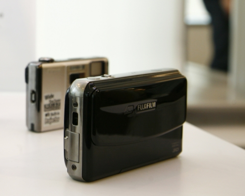 The Fujifilm FinePix REAL 3D W1 (right) is seen here, just right in front of the Nikon S1000pj, a camera that has an internal projector.