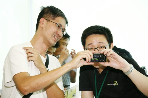 Tein Hee sharing a moment with a participant, as they discussed about the differences between photos taken with a 12.1MP camera phone (pictured here is the Samsung Pixon12), and a 12.1MP PnS camera.