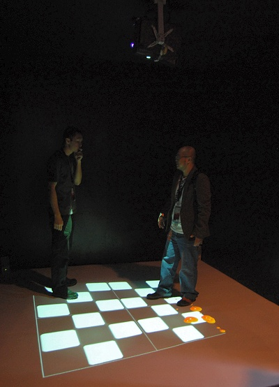 This display is of an interactive optical illusion where the board projected to the floor tilts depending where the user is and the balls on the floor follow the laws of physics as the roll around accordingly to where the board tilts. All this is facilitated by optical sensors overhead.