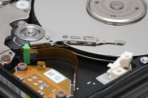 This is what a traditional hard disk looks like (image courtesy of Wikipedia). The platter, spindle, head and actuator arm are all clearly visible.