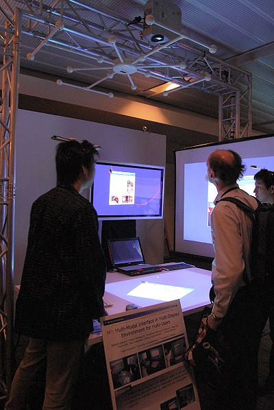 A prototype model built and engineered by the graduate students of Osaka University and others in Japan as a joint collaboration, this is a demonstration of a multi-model interface in multi-display environment for multi-users (also fondly called as M3 by the students). With a simple head mounted unit by each user, the system actually has a sensor array on top of the work area that detects the body movements and hand gestures of each user to display a perspective-aware window that each user is manipulating across multiple screens.