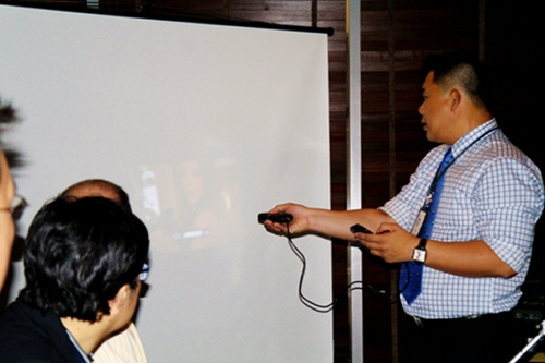 Mr. Michael Ho, Division Manager, 3M Techologies (S) Pte Ltd accompanies his demonstration, in which he screened videos on his iPhone through the 3M MPro150 pico projector, with a short back story about bringing the device along to watch his favorite movies while he was on holiday.