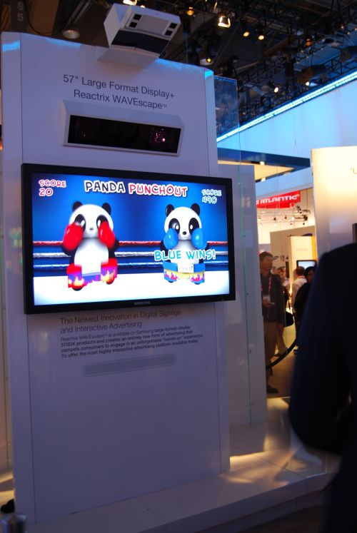"Samsung teamed up with Reactrix to demonstrate what could be a marketer's dream. Applicable as a form of interactive digital signage at retail outlets, shopping malls and so on, the Reactrix WAVEscape system is paired up with a 57"" large format Samsung display. Passers-by can wave their hands and interact with various objects on the screen based on an overhead mounted sensor that detects hand movements within a certain zone about a few inches in front of the screen."