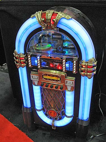 This Pacific Rim Technologies Jukebox Station is arguably the largest iPod accessory we've ever seen! Notice the iPod in the window? This huge unit has red, green and blue LED lighting system, an 80W stereo amplifier, its own woofer, mid-range drivers and tweeters, and comes with an IR remote. Heck, this one meter high, 25kg wood enclosure jukebox even has an FM radio, an S-Video port and RCA video output jacks for viewing photos or videos on a TV.