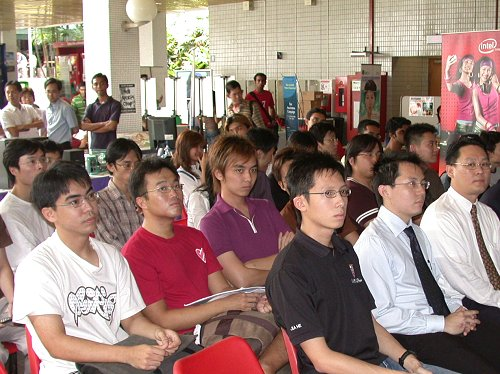 NUS students and mixed faculty members listening in on the keynote speech while gamers await their turn to start fragging.
