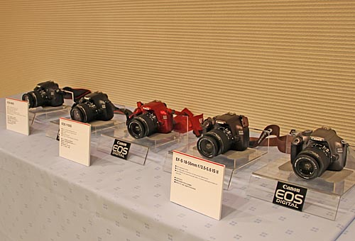 Two new DSLRs were announced: EOS 600D (far left) and EOS 1100D. The EOS 600D is the successor to the 550D. It features an 18-megapixel CMOS sensor, DIGIC 4 processor, sensitivity from ISO 100 to 6400 (expandable to 12800), 9-point AF, and 3.7 frames per second (fps) continuous shooting speed. A new Scene Intelligent Auto mode is devised, and it basically adds Picture Style Auto for better scene analysis results. Other features include a vari-angle, 1.04 million-dot, 3.0-inch LCD, up to 10x movie digital zoom, Feature Guide (on-screen description of functions and features, five creative filters, video snapshots at 2, 4, or 8-second lengths, multi aspect ratios, image rating, image resize, and integrated wireless flash control.