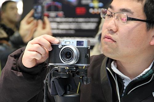 An attendee checking out Fujifilm's retro-looking FinePix X100. Despite its size, it has a 12.3-megapixel APS-C CMOS sensor. It also uses a 23 mm F2 FUJINON lens (35 mm in 35 mm equivalent), Fujifilm's EXR processor, as well as a hybrid viewfinder. And of course, analog controls for shutter speed, aperture and exposure compensation.