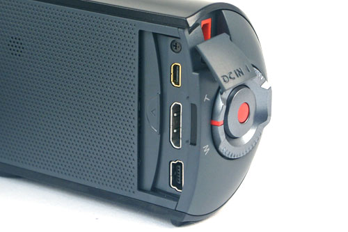 Connectors (from top): AV, HDMI, and USB. The red-colored jack behind the cover is the DC IN jack. There's no external microphone socket. Notice the hexagonal array of dots toward the top left of the image? That's the internal speaker.