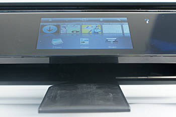 During a print job, the control panel is raised, and a small flap extends out from within. Printouts would land on this output tray extender. It stows automatically when you remove the prints.