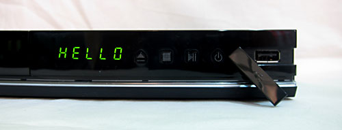 A USB 2.0 port is concealed at the front right corner. This can support USB devices such as external HDDs. Beside it are the LED display and the physical keys for the standard playback controls and the power button.