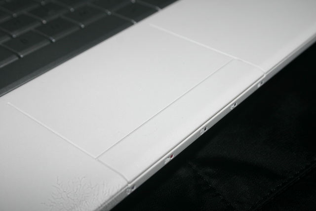 The notebook's touchpad appears seamless with the palm rest. Shown on the front are LED indicators for power, battery, hard disk drive, Wi-Fi, and the caps lock key.