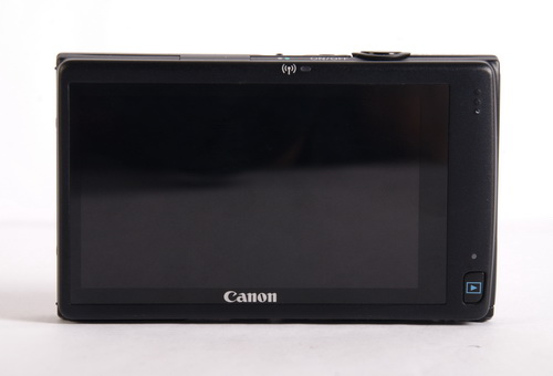 The rear side barely has a button, except for the one meant for previewing captured images. Above the touchscreen display, notice the Wi-Fi symbol, hinting at the wireless capability of the camera.