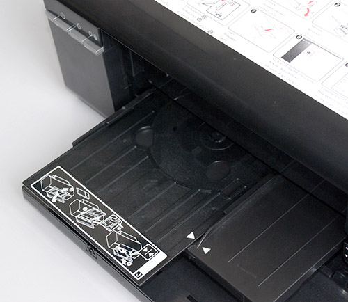 Here is a photo showing how the additional CD/DVD tray is installed. It goes on top of the paper tray. The provided instructions are easy enough to follow.