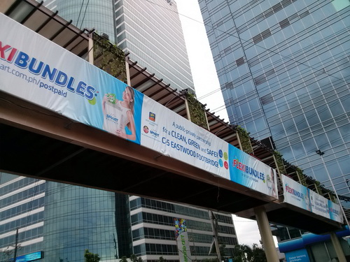 The presence of banners from Smart Communications shows the conspicuous participation of the telco in the renovation of the C-5 Eastwood Footbridge.