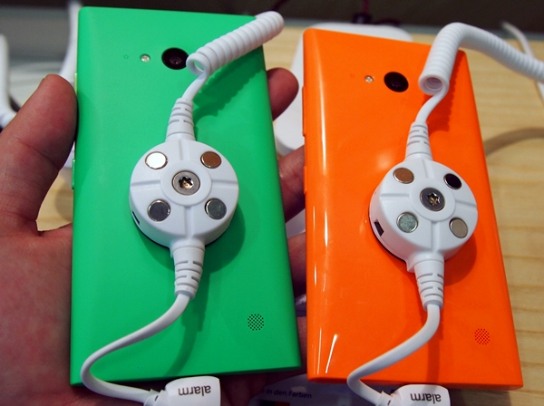 The green Lumia 730 has a matte texture on its rear while the orange model has a glossy surface.